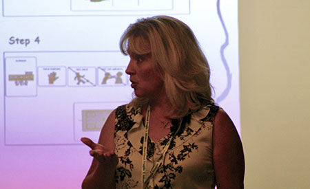 Photo of Cindi Rogers Speaking in Front of a Slide